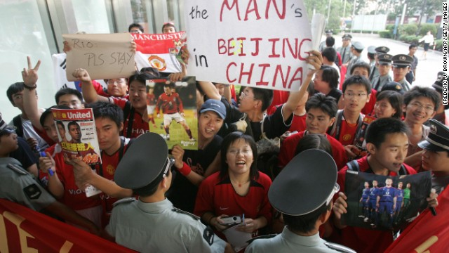 Chinese soccer fans are held back by security guards outside Manchester United's team hotel in Beijing in 2005.