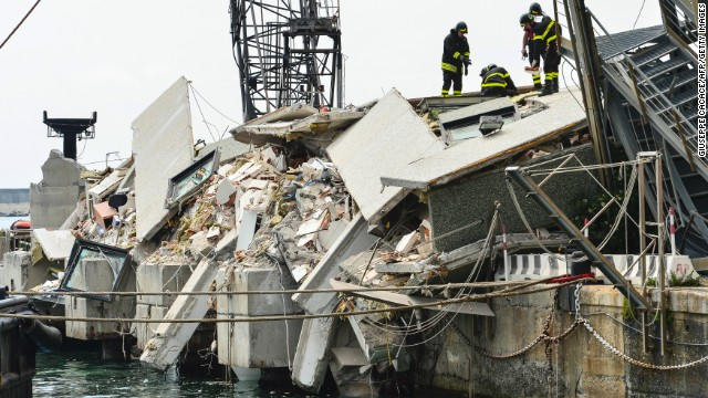 Rescue workers inspect the scene of a damaged control tower in the port of Genoa on May 8, 2013.