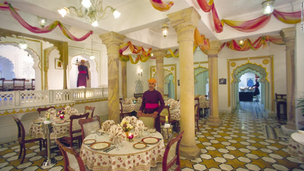 Waiters in traditional attire stand poised in the dining room of the Deogarh Mahal hotel.
