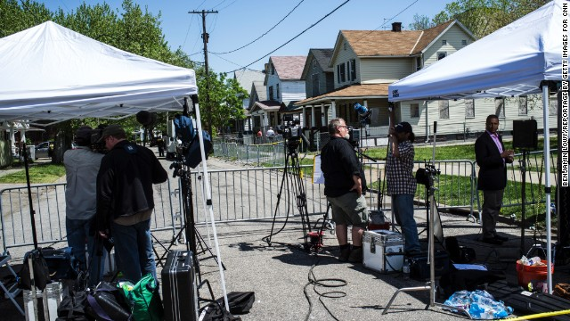 CLEVELAND, OH - MAY 9: Images from the scene of the downtrodden Cleveland neighborhood where Ariel Castro held 3 women - Amanda Berry, Gina Deesus, and Michelle Knight - for a decade. (Photo by Benjamin Lowy/Reportage by Getty Images for CNN) Other side of cordon - tents - NBC? on right  - the house is white house with black triangle g