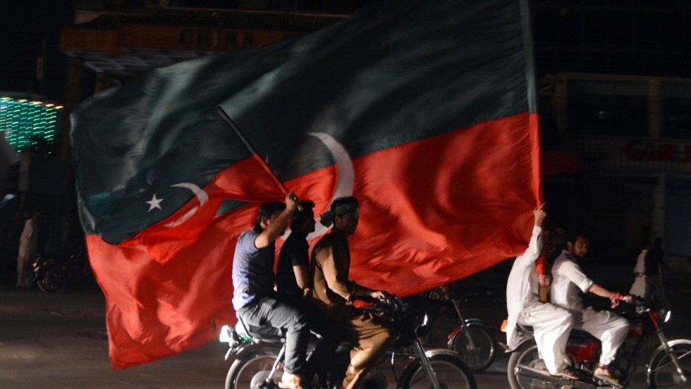 Khan supporters carry their party flags in a rally in Rawalpindi on May 12.