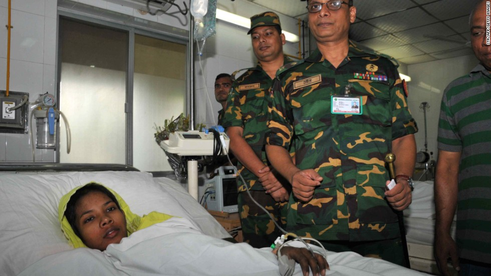 Begum rests in her hospital bed as members of the Bangladeshi military stand beside her at the Savar Combined Military Hospital in Dhaka on Saturday, May 11.