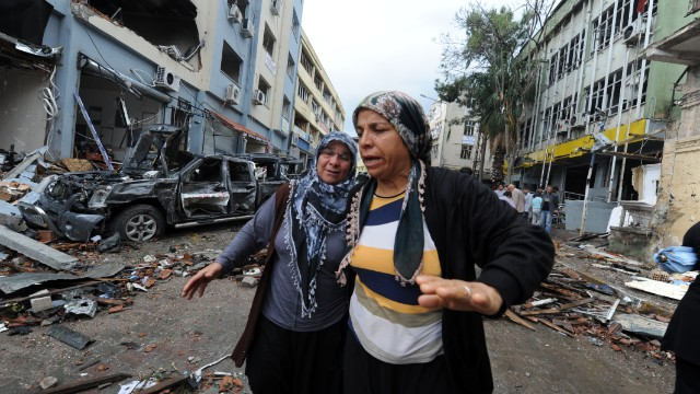 Women cry as they search on May 12, 2013 for their reletives in the debris on a street damaged by a car bomb explosion which went off on May 11 in Reyhanli in Hatay, just a few kilometres from the main border crossing into Syria. Turkey was reeling from twin car bomb attacks which left at least 43 people dead in a town near the Syrian border, with Ankara blaming pro-Damascus groups and vowing to bring the perpetrators to justice. AFP PHOTO / BULENT KILIC (Photo credit should read BULENT KILIC/AFP/Getty Images)