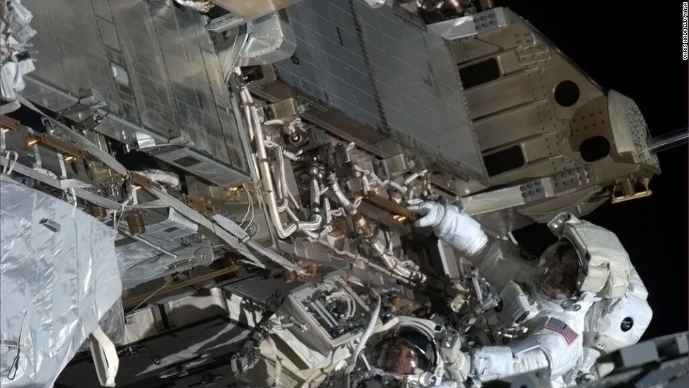 """""""Here's looking at you,"""" tweeted Hadfield about this <a href=""""https://twitter.com/Cmdr_Hadfield/status/333319320136462336"""" target=""""_blank"""">spacewalk photo opportunity</a> with Tom Marshburn, a flight engineer. """"Chris and Tom take a minute with visors to look up-sun at my camera in the window,"""" reads the May 11 post."""
