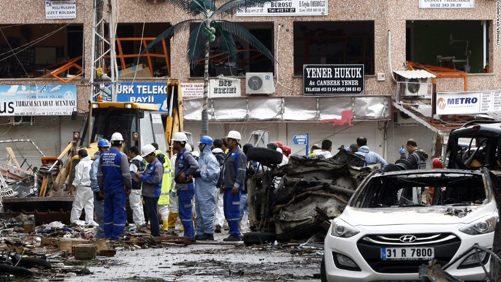 Investigators and other personnel gather near the area of the explosions. Nine suspects have been taken into custody after the attack. All are Turkish nationals.