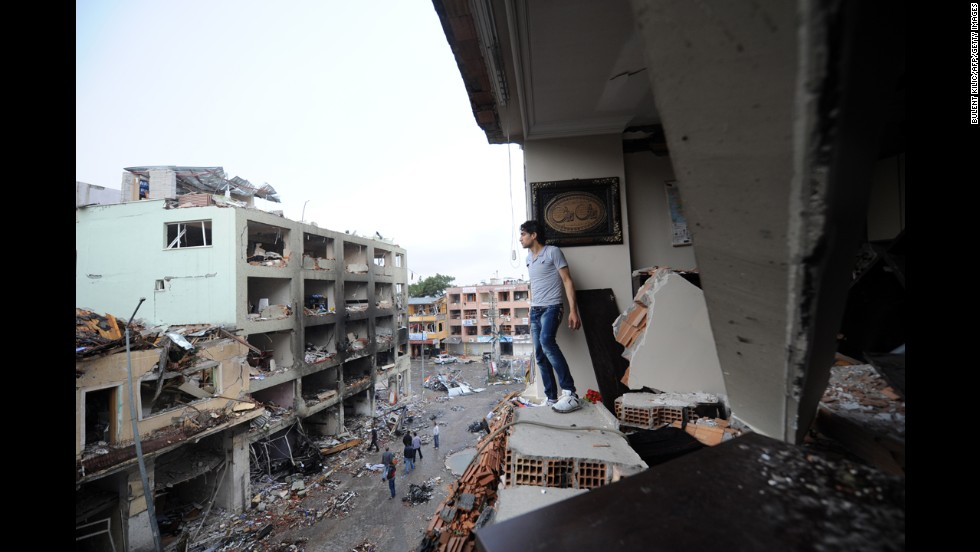A man stands in a damaged building on May 12 overlooking the scene of the bombing.