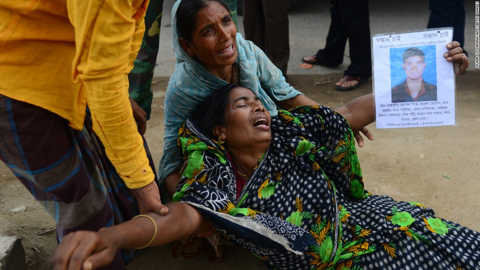 A woman cries holds a portrait of a missing relative believed to be trapped in the rubble of the Rana Plaza building on Saturday, May 11.