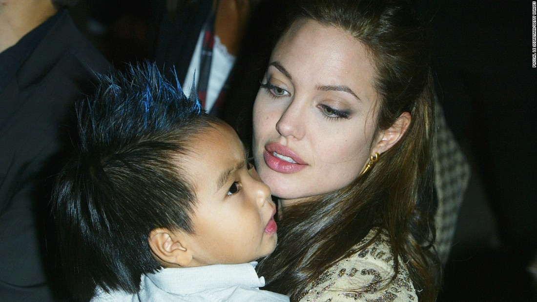 """Jolie carries her son Maddox at the world premiere of """"Shark Tale"""" in September 2004."""