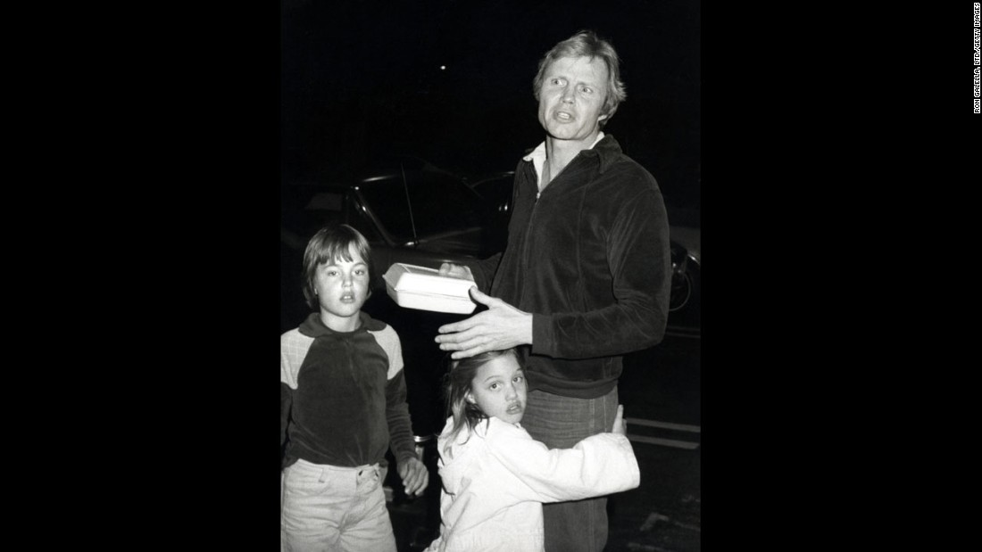 Jolie hugs her father, actor Jon Voight, in Los Angeles in 1980. Her brother, James, is at left.