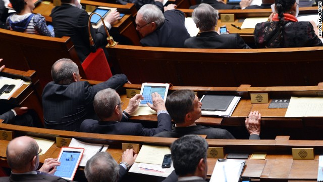 French Members of Parliament use tablets or smartphones as they attend a weekly session of questions to the government at the National Assembly in Paris