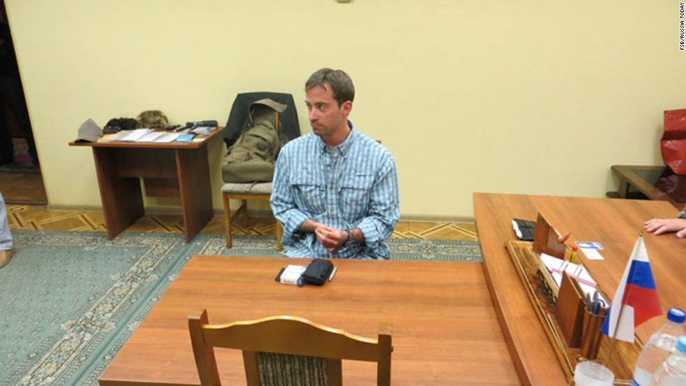 The man sits behind a desk after being detained.