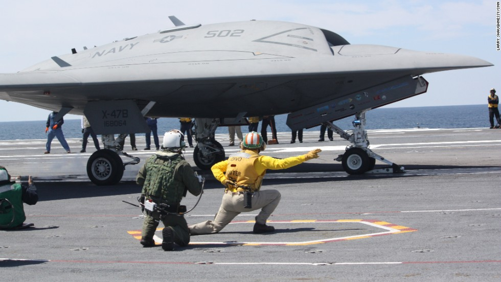 The X-47B drone sits ready to launch from the deck of the aircraft carrier.