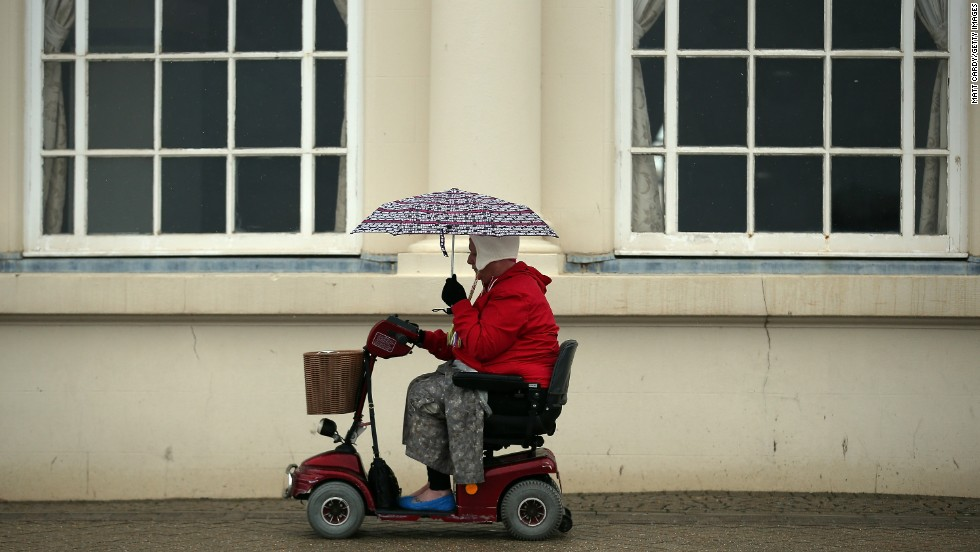 A woman passes along the seafront as the rain falls in Weston-Super-Mare, England, on Tuesday, May 14.