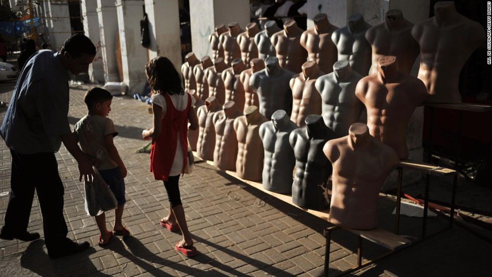Children walk past a stall at the Rashid Street market in the center of Tripoli on August 29, 2011.