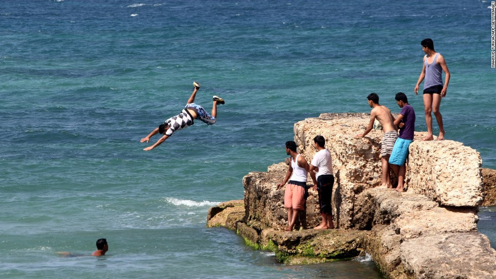 A young man jumps into the waters of the Mediterranean Sea off the coast of Tripoli on April 30, 2012.