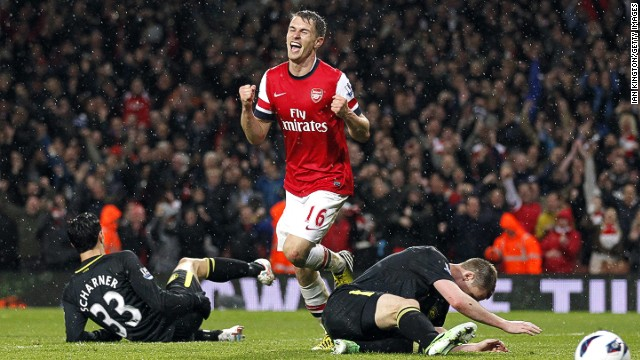 Aaron Ramsey dances his way past dejected Wigan defenders as he seals their fate with Arsenal's fourth goal of the night.