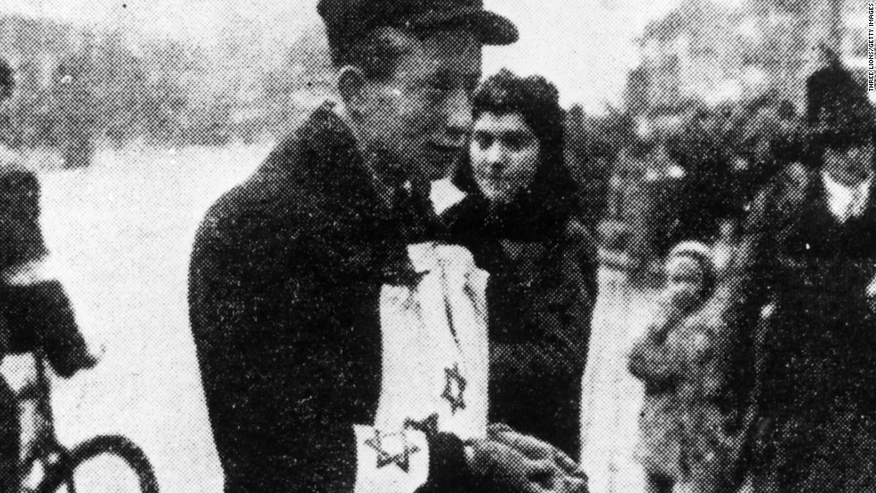 A street vendor in Warsaw ghetto sells yellow armbands featuring the star of David, which had to be worn visibly by all Jews in Warsaw at all times.