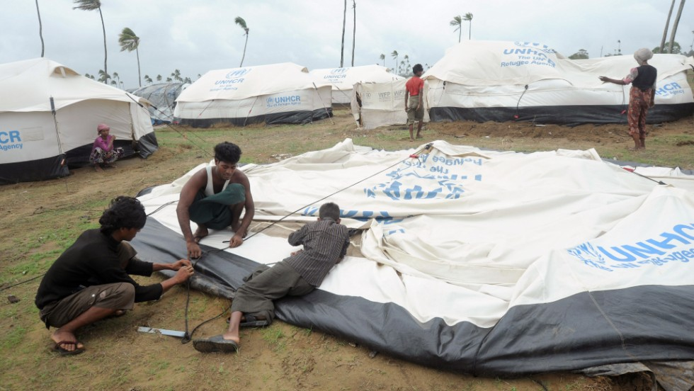 Rohingya men dismantle their tent as they prepare to move to a safer area on May 16.
