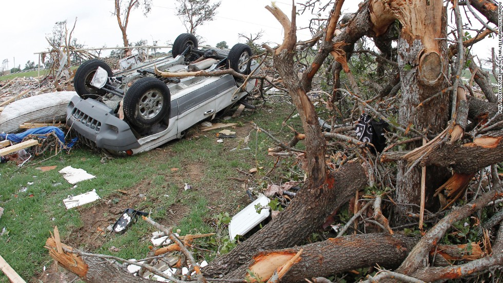 An upturned vehicle lies next to an uprooted tree on Thursday, May 16, in Granbury, Texas.