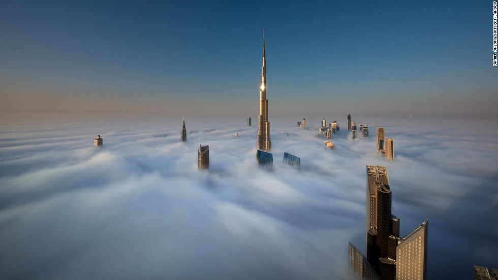 The windows of the Burj Khalifa catch a glint of sunlight as the skyscrapers of Dubai stand high above the clouds in this image taken from the 79th floor of the Index Tower.