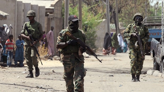 "This picture taken on April 30, 2013 shows Nigerian troops patrolling in the streets of the remote northeast town of Baga, Borno State. Nigeria's military said on May 16, 2013 that it was ready to launch air strikes against Boko Haram Islamists as several thousand troops moved to the remote northeast to retake territory seized by the insurgents. A force of ""several thousand"" soldiers along with fighter jets and helicopter gunships have been deployed for the offensive in Borno, Yobe and Adamawa state, he added."