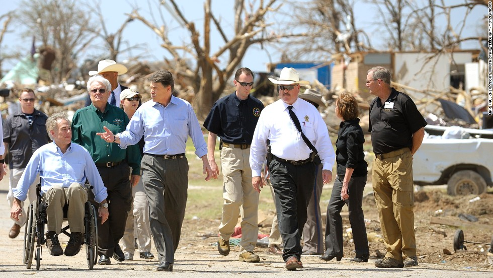 Texas Gov. Rick Perry, center, and Texas Attorney General Greg Abbott, left, survey the tornado damage in the Rancho Brazos Estates subdivision near Granbury, Texas, on Friday, May 17. At least six people were killed in a string of tornadoes that struck overnight Wednesday in North Texas.