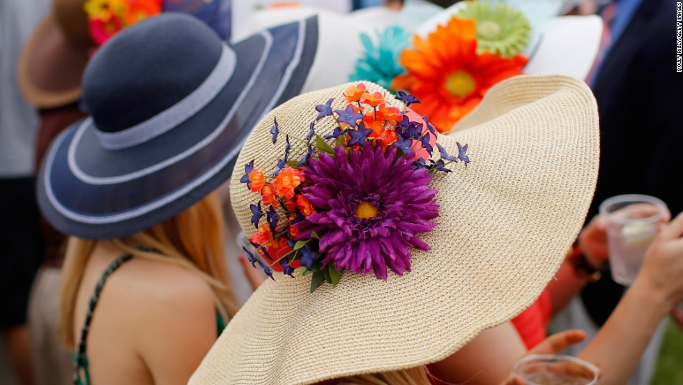 Fans wearing festive hats enjoy the festivities prior to the Preakness Stakes.