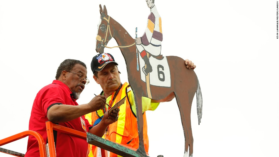 Workers paint the weather vane at the Pimlico Race course to match the colors worn by Oxbow and his jockey.