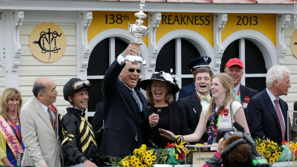 Trainer D. Wayne Lukas celebrates, holding the trophy aloft, in the Winner's Circle.