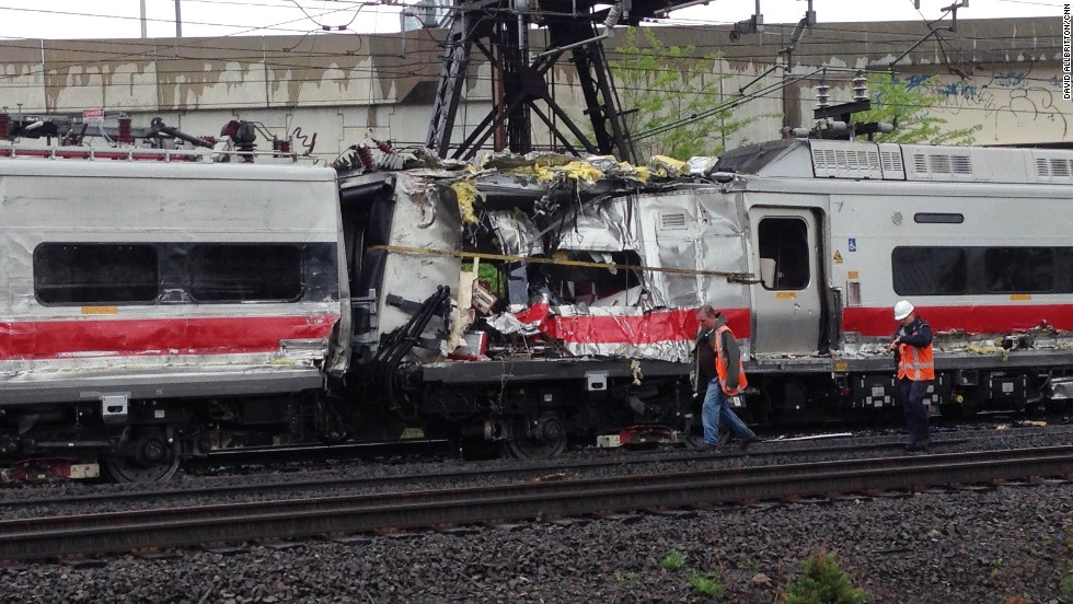 Investigators walk past two train cars damaged in the collision on Friday, May 17.