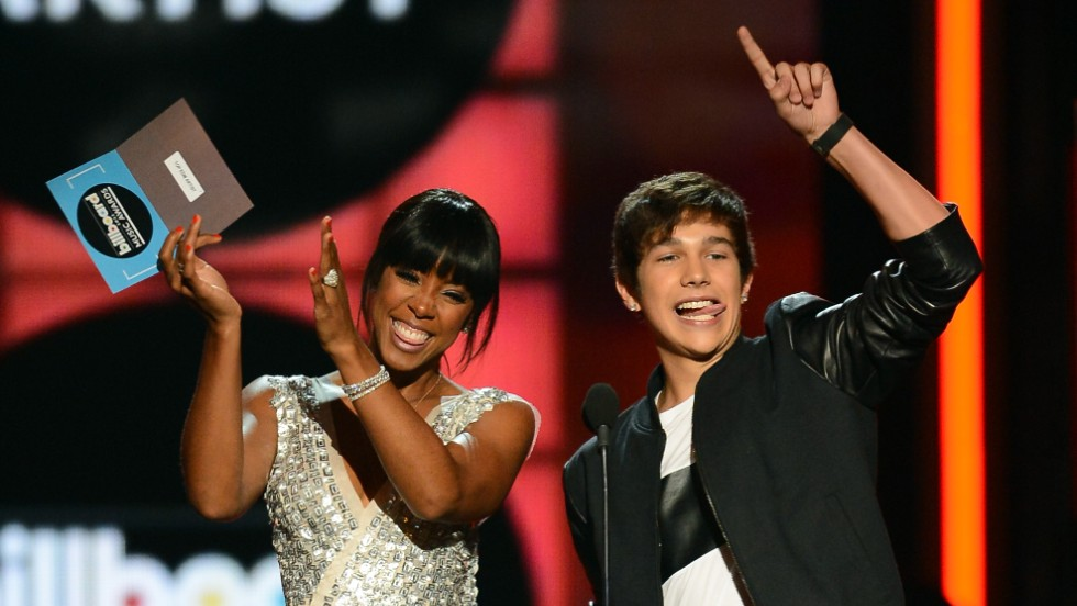 Presenters Kelly Rowland and Austin Mahone speak onstage.