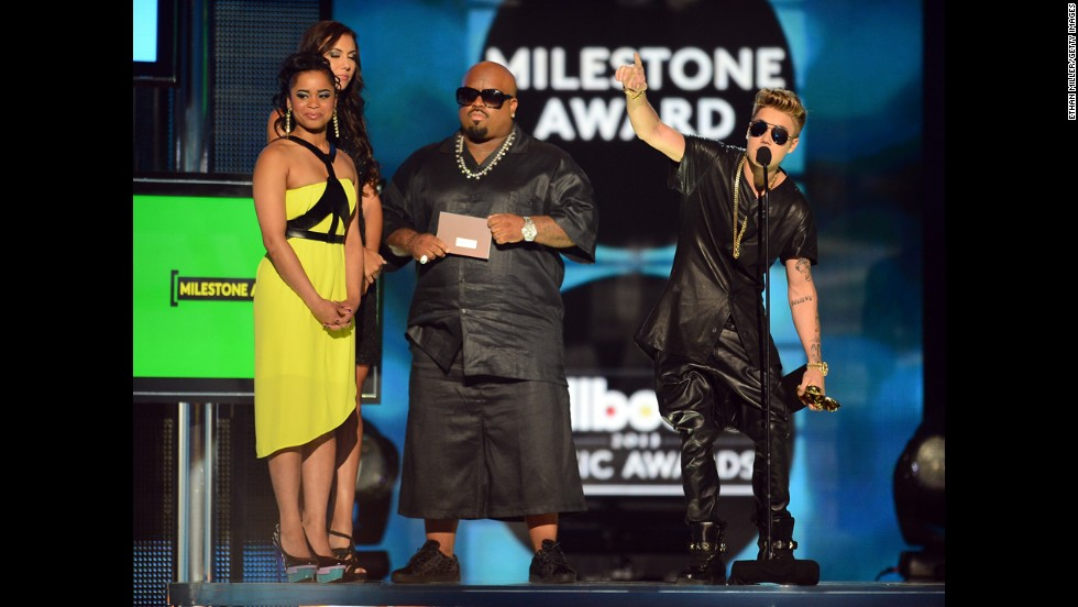 Contest winner Shaniece Cole, musician CeeLo Green and Milestone Award winner Justin Bieber stand onstage.