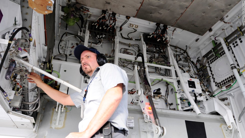 A United Airlines maintenance worker examines a hydraulic line.