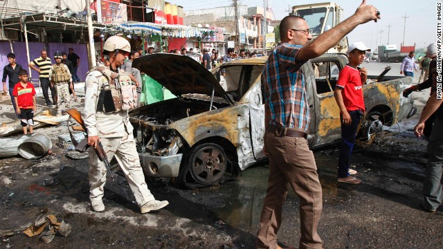 Iraqi citizens and soldiers inspect the scene of one of two car bombings in Basra on Monday.