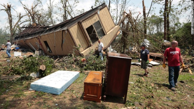 SHAWNEE, OK - MAY 20:  Volunteers help clean out Jean McAdams' mobile home after it was overturned by a tornado May 20, 2013 near Shawnee, Oklahoma. A series of tornados moved across central Oklahoma May 19, killing two people and injuring at least 21. (Photo by Brett Deering/Getty Images)