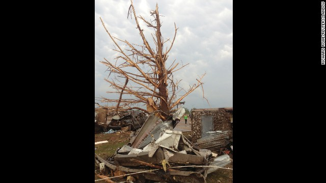 Image #: 22426417    A shredded tree stands amid debris after a massive tornado touched down in the town of Moore, near Oklahoma City, Oklahoma May 20, 2013.  A huge tornado with winds of up to 200 miles per hour (320 kph) tore through the Oklahoma City suburb of Moore on Monday, ripping up at least two schools and leaving a wake of tangled wreckage as a dangerous storm system threatened as many as 10 U.S. states.   REUTERS/Richard Rowe (UNITED STATES - Tags: DISASTER ENVIRONMENT)       Reuters /STRINGER /LANDOV