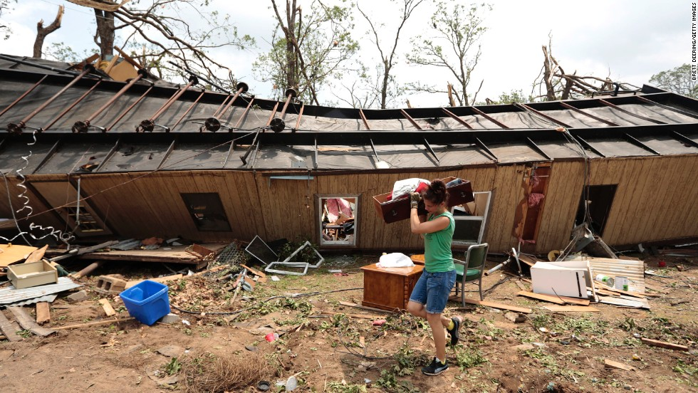 A volunteer helps clean up a mobile home on May 20 after it was overturned on a day earlier near Shawnee, Oklahoma.