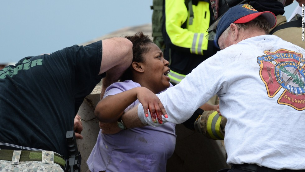 Rescue workers help free one of more than a dozen people who were trapped at a medical center in Moore on May 20.