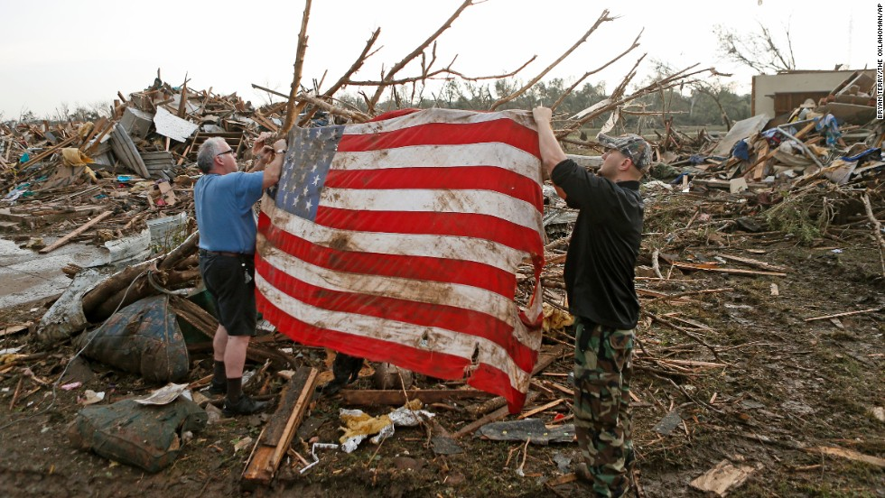 Men tie an American flag on debris in a neighborhood off Telephone Road in Moore on May 20.