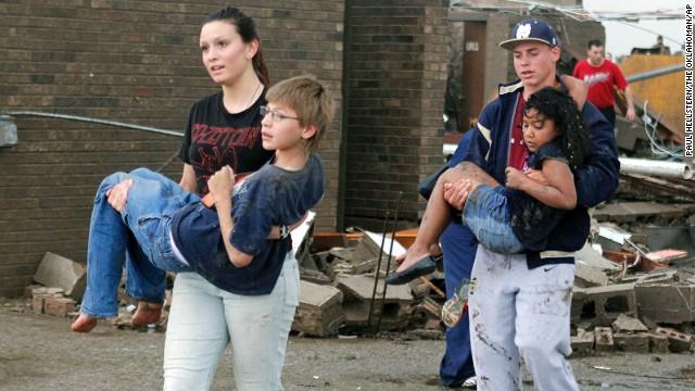 Teachers carry children away from Briarwood Elementary School.