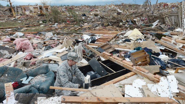 Air Force Airman First Class Justin Acord sifts through the rubble of his father-in-law's home in Moore, Oklahoma, 21 May 2013.