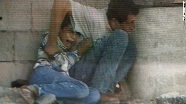 TV grab from France 2 footage of Israeli-Palestinian clashes in Netzarim in the Gaza Strip 29 September 2000 shows Jamal Al-durra and his son Mohammed, 12, hiding behind a barrel to protect themselves from Israeli-Palestinian cross fire. The boy is screaming in panic as shots hit the wall over their heads. Seconds later he was fatally struck in the abdomen. Seriously wounded, the father lost consciousness, was hospitalized in Gaza and is expected to recover. (Photo credit should read /AFP/Getty Images)