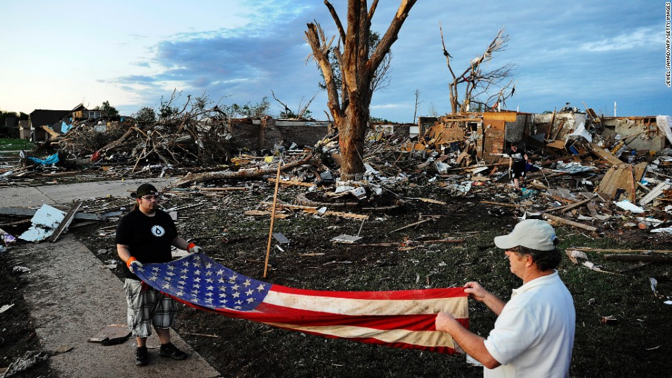 Two men fold an American flag found in the debris of a house on May 21 in Moore.