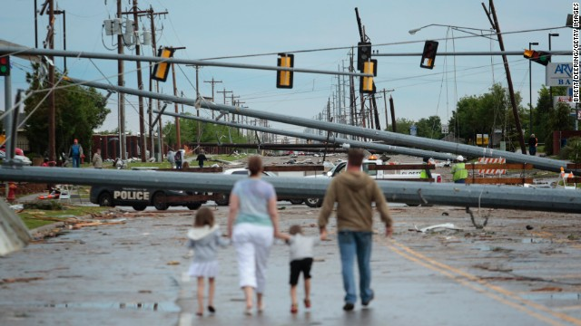 Downed utility poles block the road as a family walks down Sante Fe Avenue on May 21 in Moore, Oklahoma.