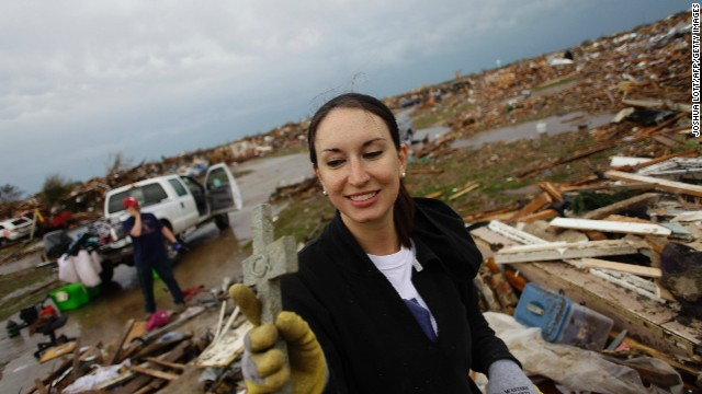 Kalissa Graham reacts after finding a cross in the the rubble of her destroyed home on May 21, 2013 in Moore, Oklahoma. Families returned to a blasted moonscape that had been an American suburb Tuesday after a monstrous tornado tore through the outskirts of Oklahoma City, killing at least 24 people. Nine children were among the dead and entire neighborhoods vanished, with often the foundations being the only thing left of what used to be houses and cars tossed like toys and heaped in big piles
