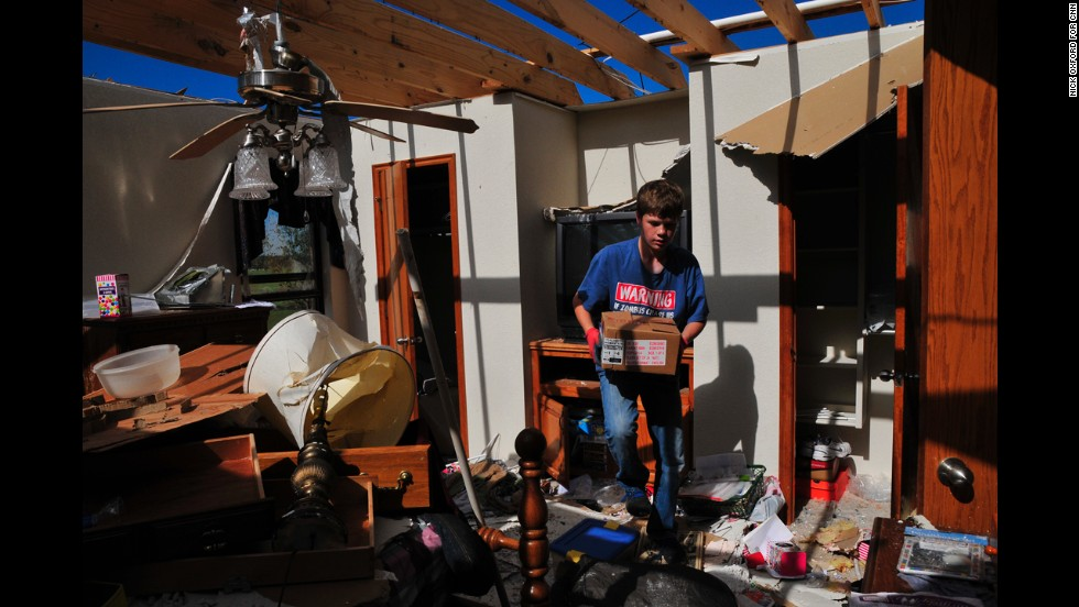 Jake English, 12, cleans up retired school counselor Kay Taylor's home on May 22 in south Oklahoma City, just west of Moore. The storm was part of a tornado outbreak that began in the Midwest and Plains on Sunday, May 19.