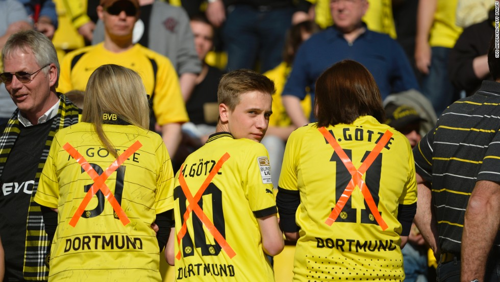 Dortmund fans wear replica jerseys of midfielder Mario Goetze with a X though them following his controversial transfer to bitter Bundesliga rivals Bayern Munich.