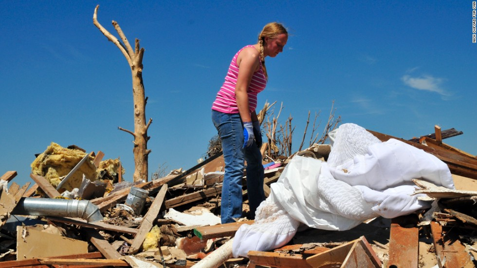 Kelcy Trowbridge searches for family keepsakes in the rubble of her home.