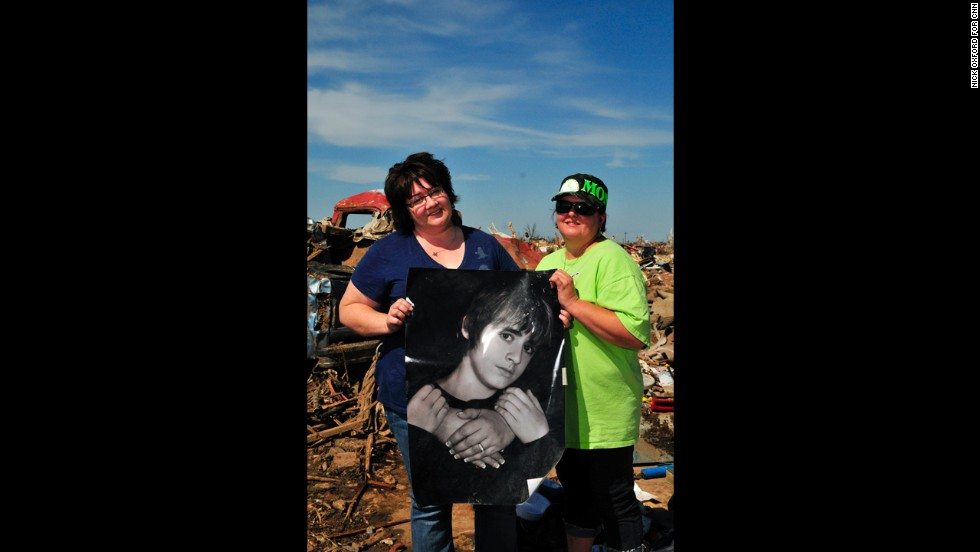 Jennifer Nutty-Marquez, left, and Jamie Plunk saved a poster of Nutty-Marquez's son, Caleb, from the wreckage of their home.