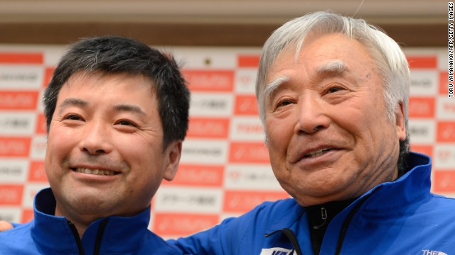 Yuichiro Miura (R) poses with his son Gota Miura (L) for photographers during a press conference in Tokyo on March 22.